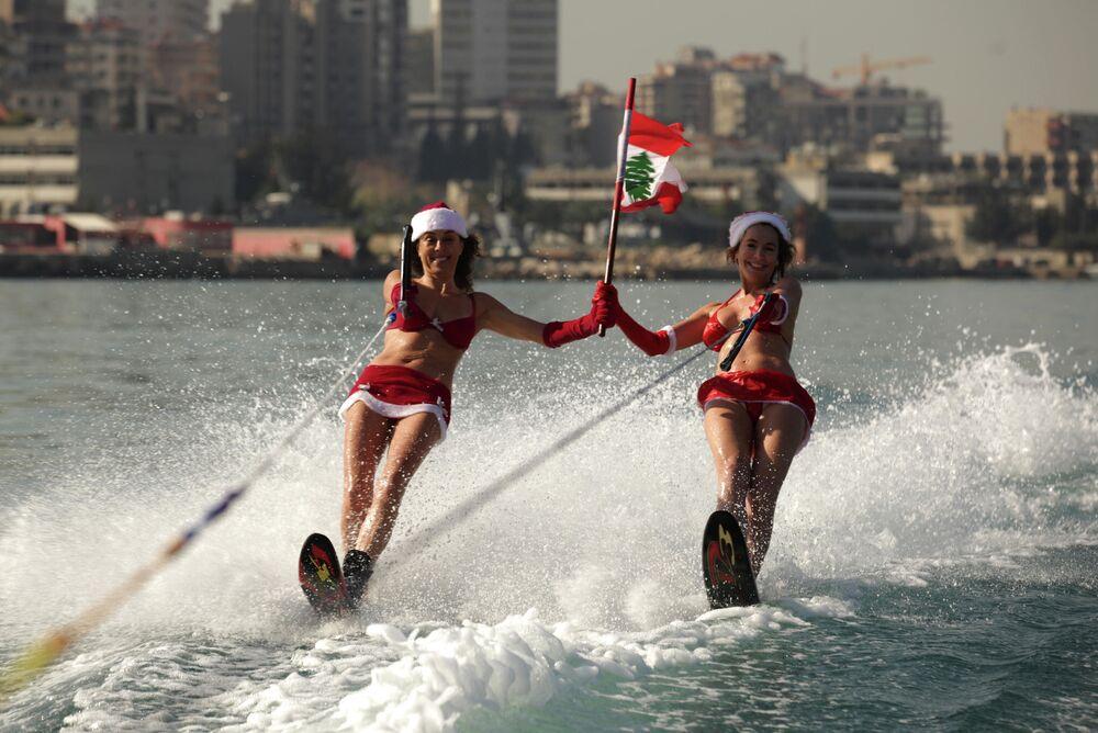 Due ragazze vestite da Babbo Natale mentre fanno sci nautico in Libano