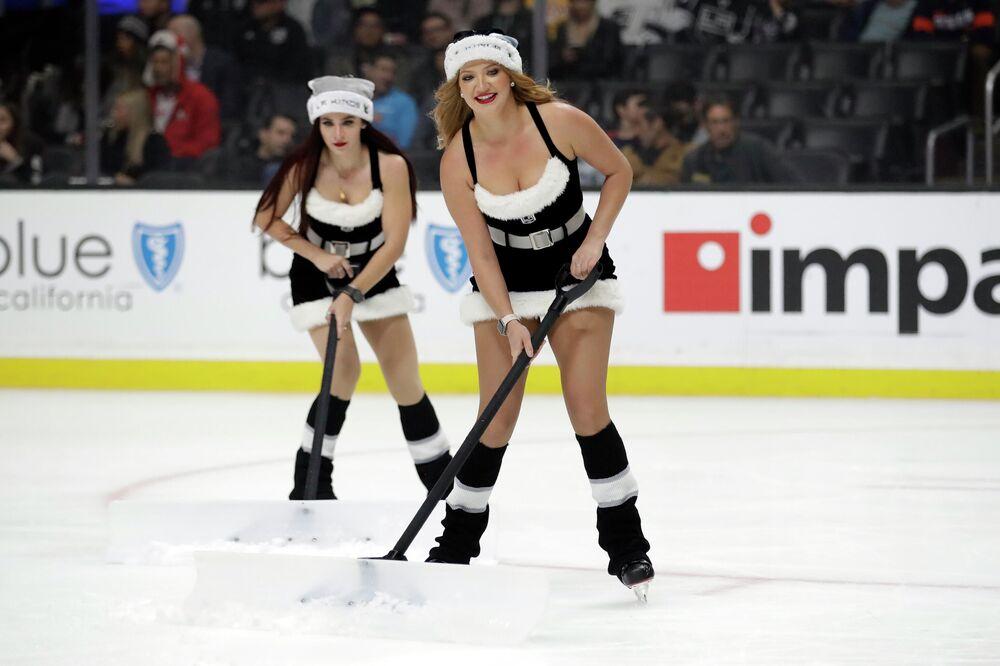 Ragazze puliscono il ghiaccio durante una partita di hockey a Los Angeles, USA