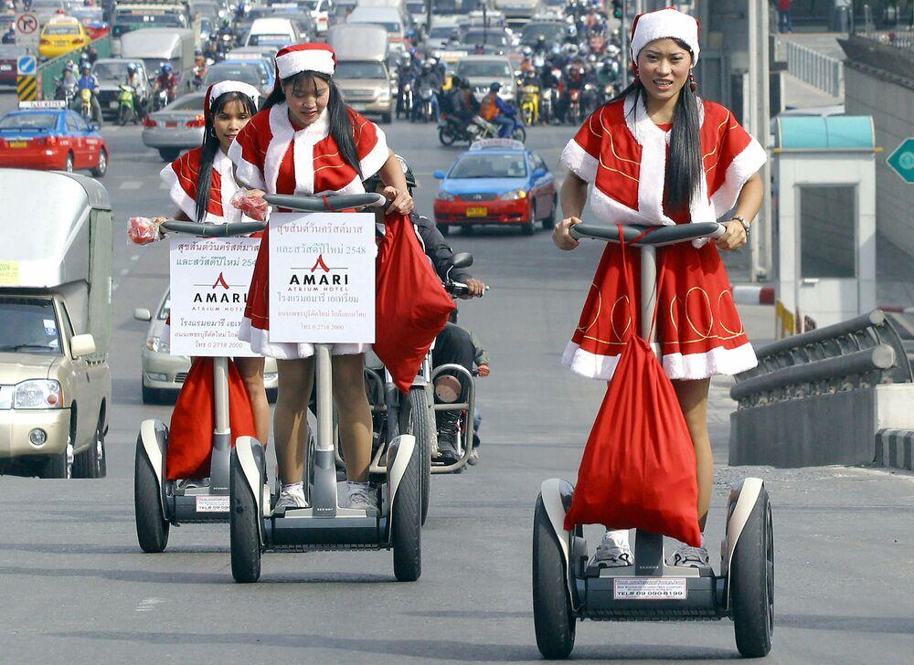 Impiegate di un hotel vestite in costume di Babbo Natale si dirigono per fare regali ai residenti a Bangkok, Thailandia