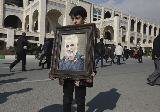 A boy carries a portrait of Iranian Revolutionary Guard Gen. Qassem Soleimani