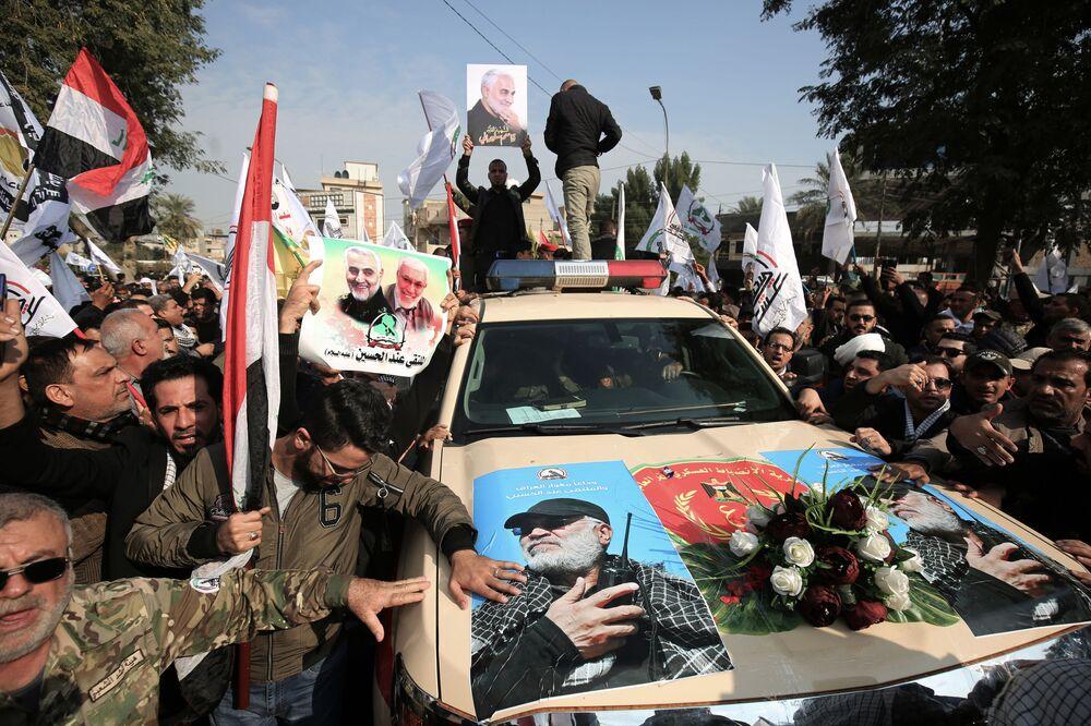 Auto con gli immagini del militare iracheno Abu Mahdi al-Muhandis durante una cerimonia funebre a Baghdad