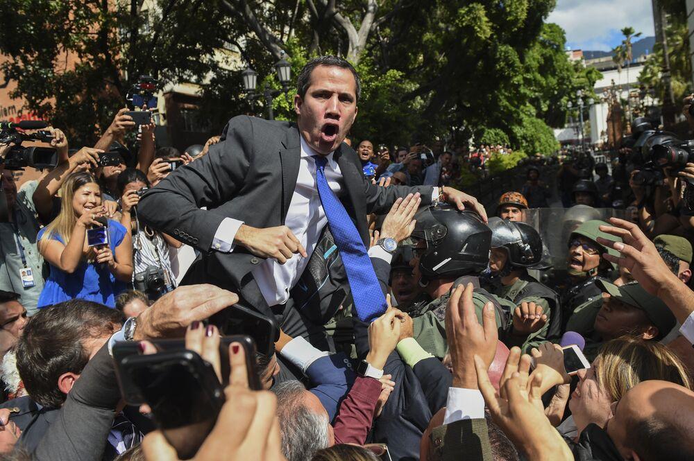 Il presidente autoproclamatosi ad interim venezuelano Juan Guaido circondato da giornalisti in una via vicino l'Assemblea nazionale, Caracas