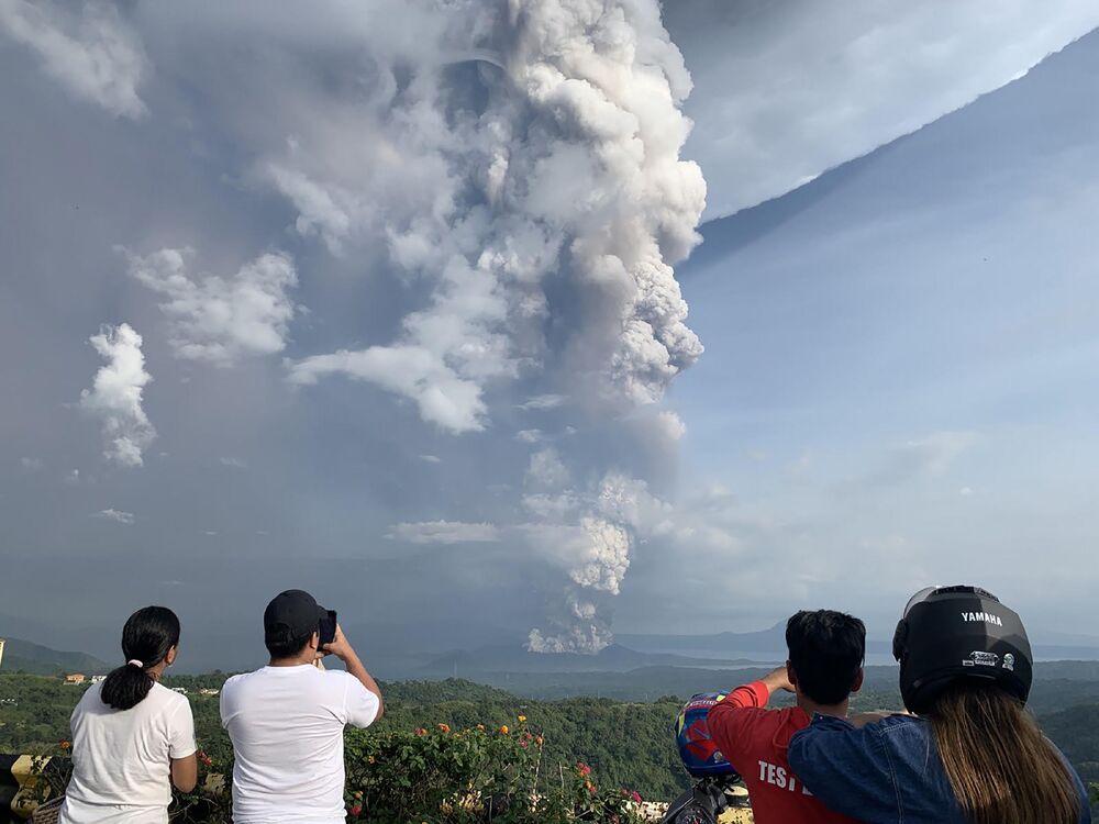 Persone fotografano l'eruzione del vulcano Taal vista dalla città di Tagaytay, Filippine, il 12 gennaio 2020