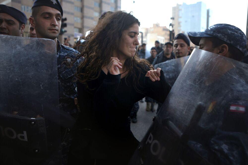 Una manifestante libanese contro la corruzione è circondata dalla polizia antisommossa durante una manifestazione nel centro di Beirut, il 14 gennaio 2020