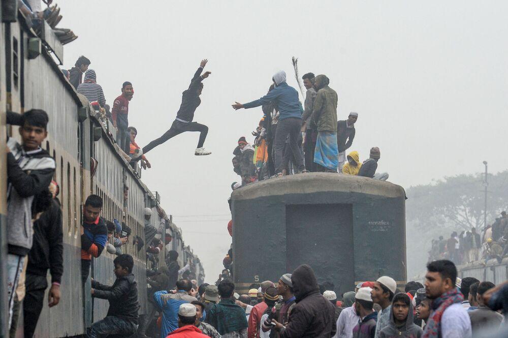 Un uomo salta da un treno all'altro su mentre arriva insieme ad altri per prendere parte al raduno musulmano annuale Biswa Ijtema, considerato il secondo raduno dopo il Haij, a Tongi, a nord della capitale Dacca, Bangladesh, il 12 gennaio il 2020
