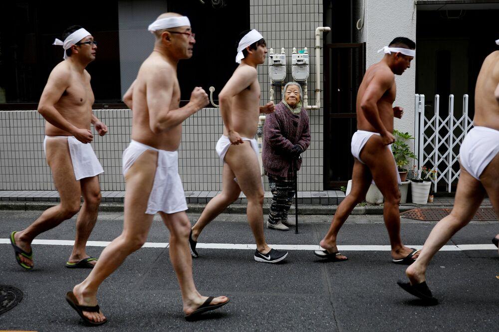 Una donna osserva uomini che si preparano a fare il bagno in acqua ghiacciata durante una cerimonia per purificare le loro anime e augurare buona salute nel nuovo anno a Tokyo, Giappone, il 12 gennaio 2020