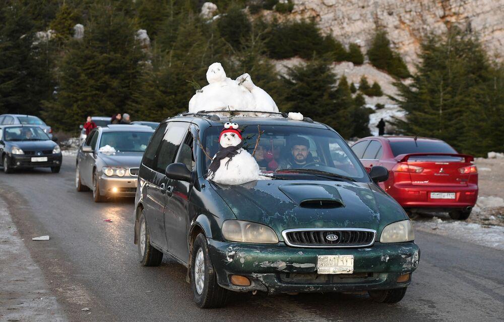 I siriani usano le auto per trasportare la neve dalle montagne nella parte montuosa di Laodicea