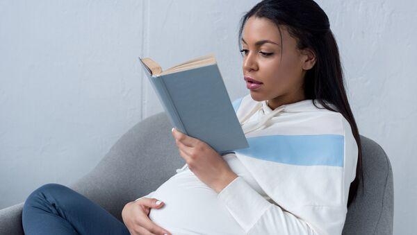 Беременная женщина, читающая книжку - Sputnik Italia
