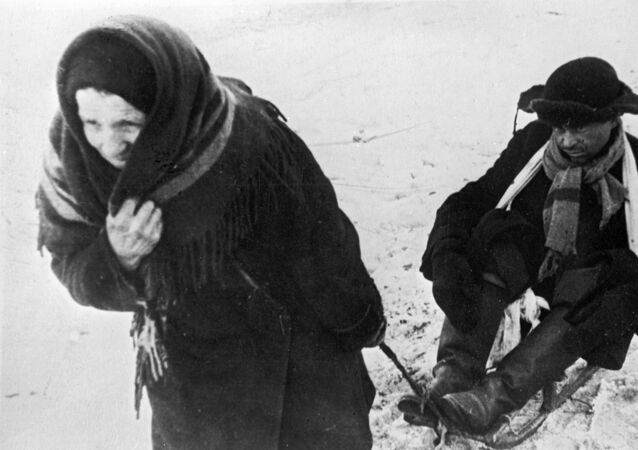 Una donna trasporta suo marito, indebolito dalla fame, su una slitta durante i giorni dell'assedio di Leningrado