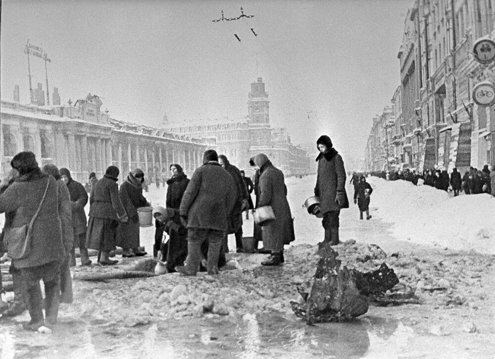 I residenti di Leningrado assediata raccolgono dell'acqua dai buchi nell'asfalto provocati dai bombardamenti