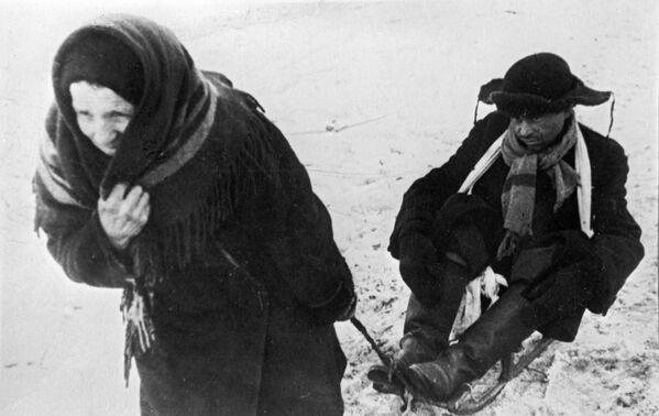 Una donna trasporta suo marito, indebolito dalla fame, su una slitta durante i giorni dell'assedio di Leningrado - Sputnik Italia
