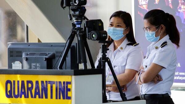 Сотрудники аэропорта в масках следят за тепловым сканером в международном аэропорту Ninoy Aquino на Филиппинах - Sputnik Italia