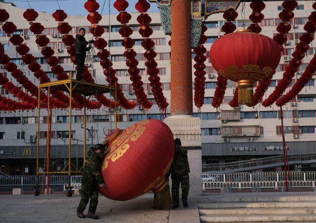 I lavoratori smantellano le decorazioni dopo la decisione di cancellare un mercantino per festeggiare il nuovo anno lunare a Pechino, Cina