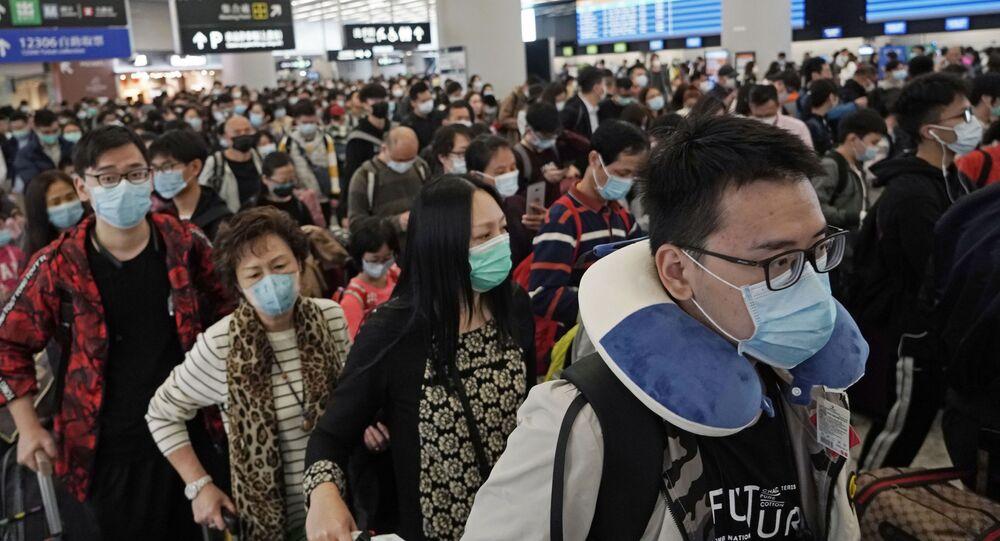 Passeggeri in maschere alla stazione ferroviaria a Hong Kong