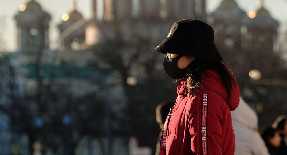 Una turista cinese in maschera a San Pietroburgo