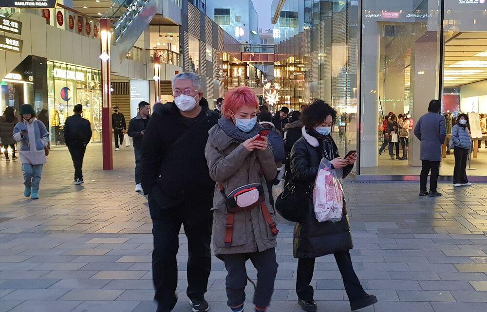 Passanti con maschere protettive a Pechino.