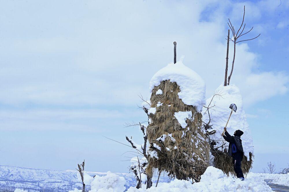 Un indiano toglie la neve da un pagliaio.