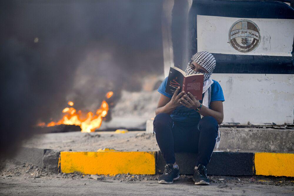 Un manifestante legge un romanzo vicino alle gomme incendiate nella città di Najaf, in Iraq.