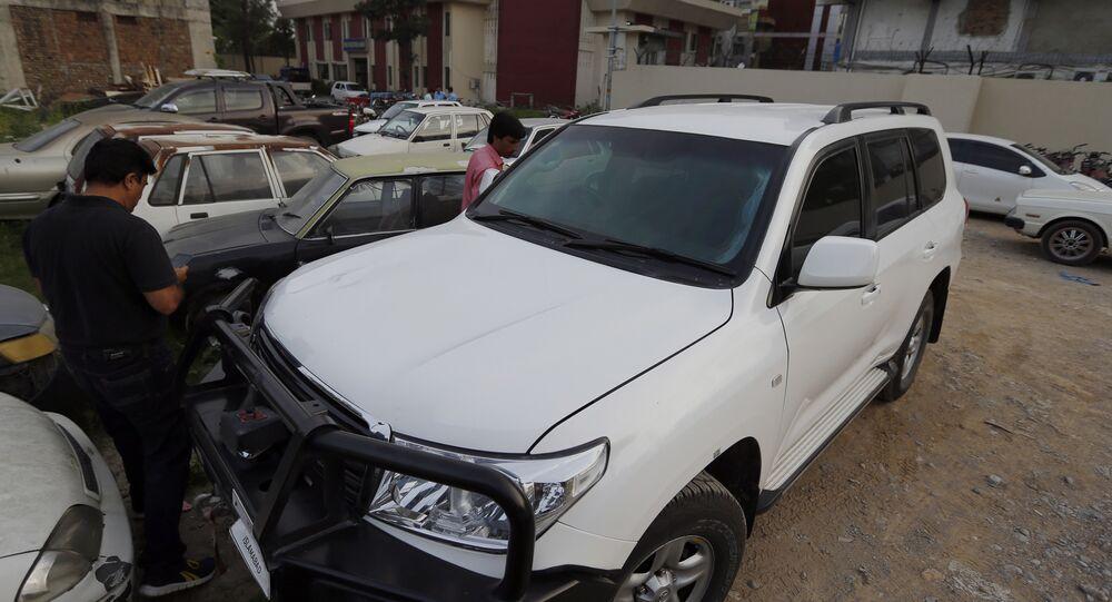 Un giornalista pakistano esamina l'auto di un diplomatico USA parcheggiata dentro una stazione di polizia, in seguito a un incidente a Islamabad, Pakistan, sabato 7 aprile 2018