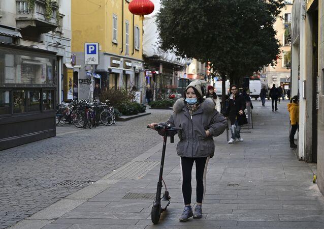 Una ragazza con una maschera nel quartiere cinese di Milano