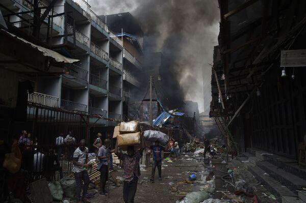 Ambulanti portano in salvo la merce durante un incendio in un mercato di Lagos, in Nigeria. - Sputnik Italia