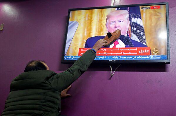 Un palestinese mette uno stivale sullo schermo del televisore in un caffè di Hebron (Al Khalil) dal quale Donald Trump parla del suo piano per un accordo in Medio Oriente. - Sputnik Italia