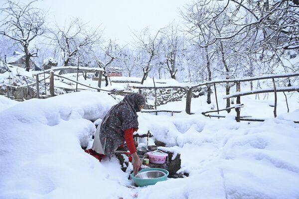 Donna lava i piatti a Srinagar, in India, dopo una nevicata - Sputnik Italia