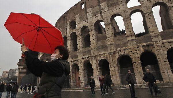 Un turista in maschera si fa un selfie davanti al Colosseo - Sputnik Italia