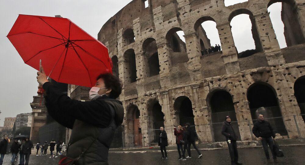 Un turista in maschera si fa un selfie davanti al Colosseo