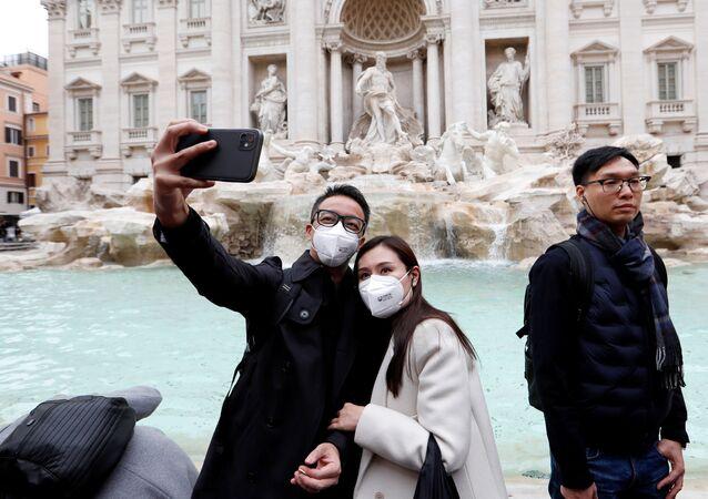 Turisti in maschere si fanno un selfie a Roma