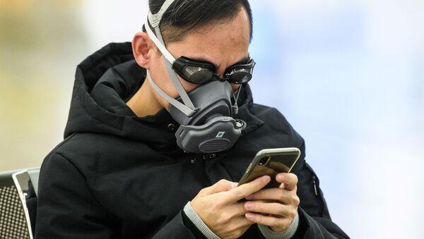 Un passeggero in maschera e occhialini da nuoto per proteggersi dal coronavirus a Hong Kong - Sputnik Italia