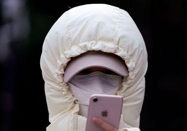 Una donna con una maschera protettiva a Shanghai