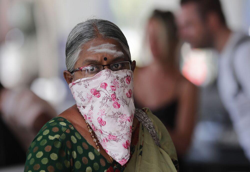 Un'indiana anziana in maschera fatta con un fazzolletto  all'aeroporto di Colombo, Sri Lanka.