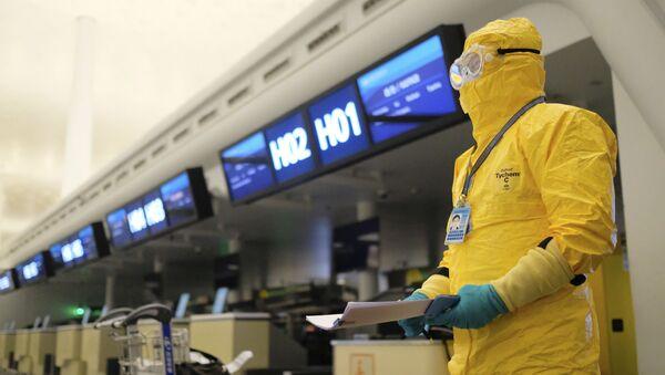 Un dipendente indossa un costume protettivo a Wuhan, Cina - Sputnik Italia