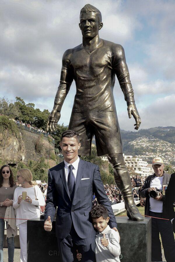 Cristiano Ronaldo con suo figlio sotto una statua di se stesso durante la cerimonia di apertura nella sua città natale di Funchal, Portogallo, 2014 - Sputnik Italia