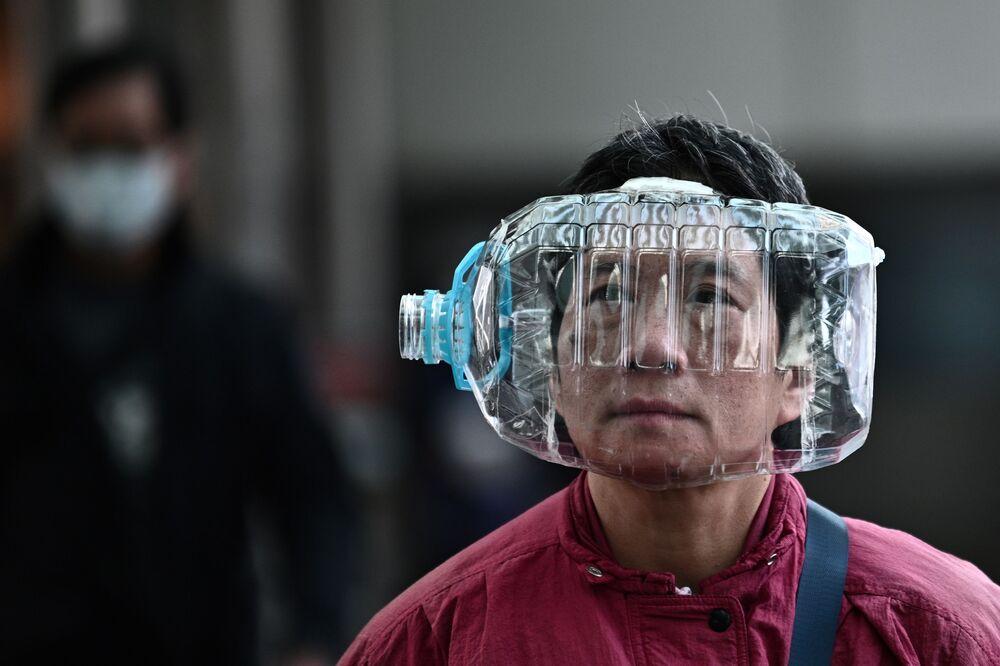 Un uomo a Hong Kong utilizza una bottiglia di plastica come maschera protettiva.