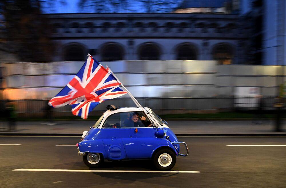 Un uomo sventola la bandiera della Gran Bretagna nel centro di Londra, festeggiando la Brexit.
