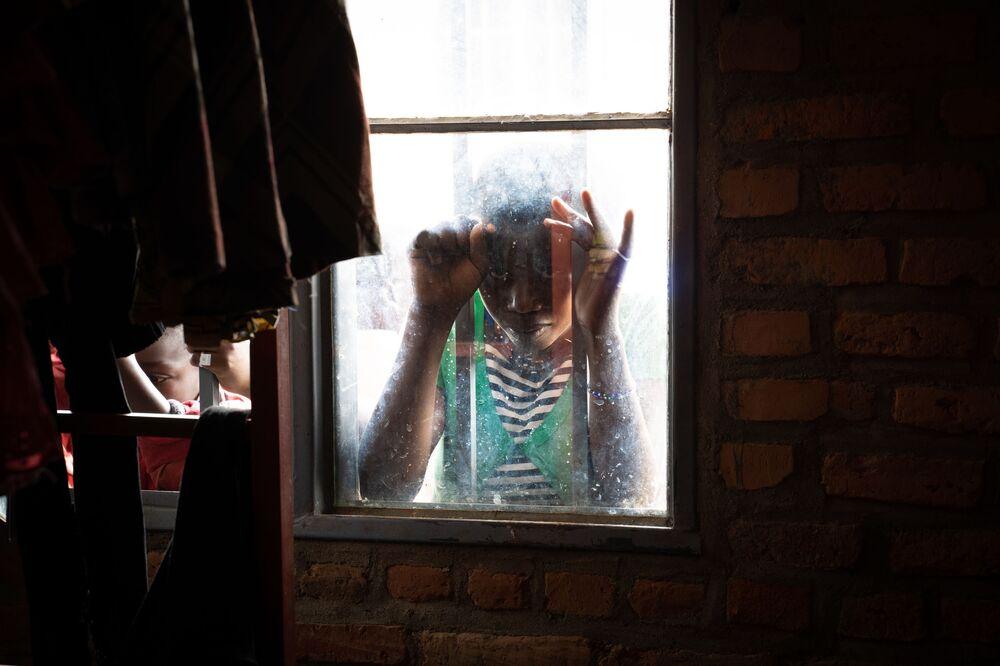 Una ragazza dietro alla finestra del campo rifugiati a Nyarushihi, in Ruanda.