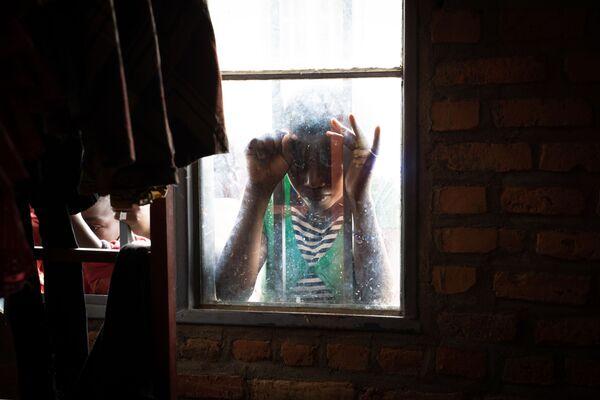 Una ragazza dietro alla finestra del campo rifugiati a Nyarushihi, in Ruanda. - Sputnik Italia