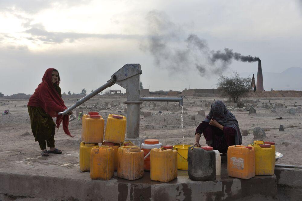 Ragazze raccolgono l'acqua dal pozzo nella città afghana di Jalalabad.