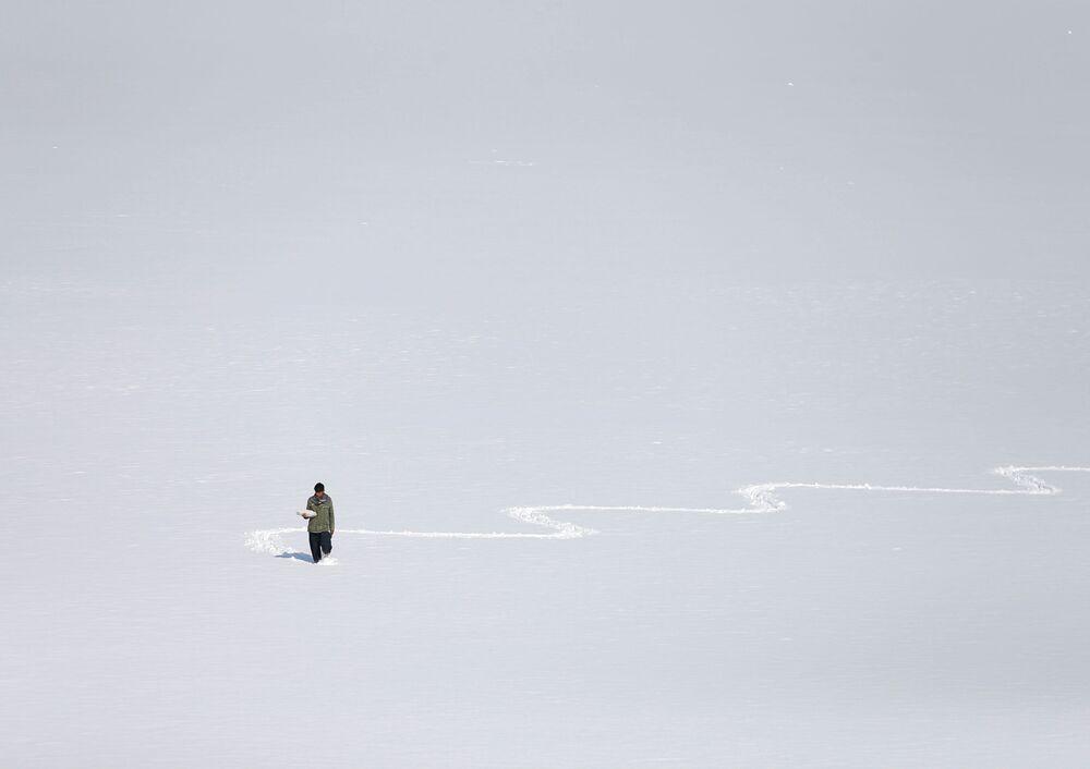 Un uomo afghano sul lago Qargha coperto di neve a Kabul, in Afghanistan.