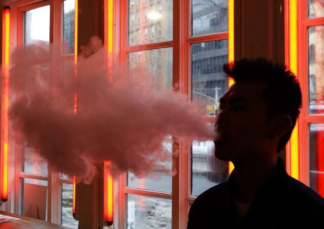 Man exhales vapor from an e-cigarette