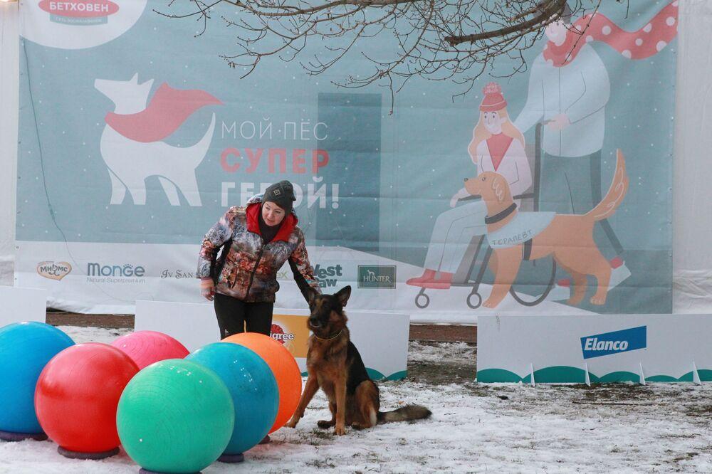 Una padrona con il suo pastore tedesco al festival Il mio cane è un supereroe a Mosca.