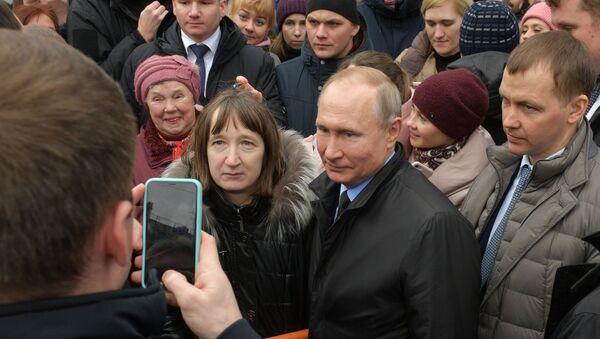 Vladimir Putin fa una foto con un'abitante di San Pietroburgo - Sputnik Italia