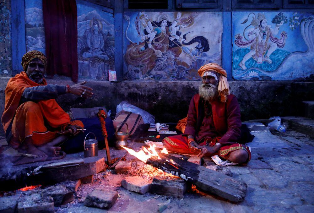 Sadhu indù (uomini santi) siedono accanto al fuoco nel tempio di Pashupatinath un giorno prima del festival Shivaratri a Kathmandu, Nepal, il 20 febbraio 2020