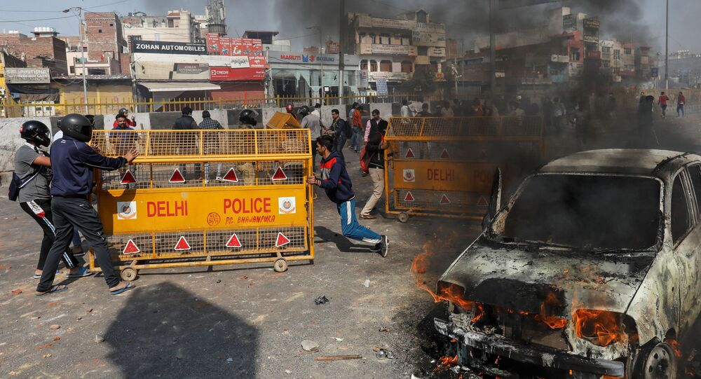 People supporting a new citizenship law push police barricades during a clash with those opposing the law in New Delhi India, February 24, 2020