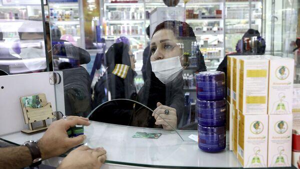Una cliente in mascherina in una farmacia di Teheran - Sputnik Italia