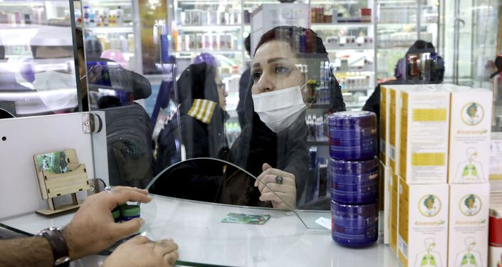 Una cliente in mascherina in una farmacia di Teheran