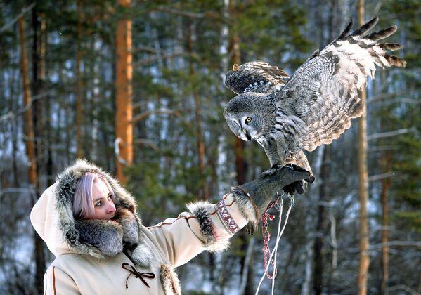 La guardiana dello zoo Daria Cherepanova con Mykh, grande gufo grigio, durante l'allenamento allo zoo Royev Ruchey a Krasnoyarsk, Russia - Sputnik Italia