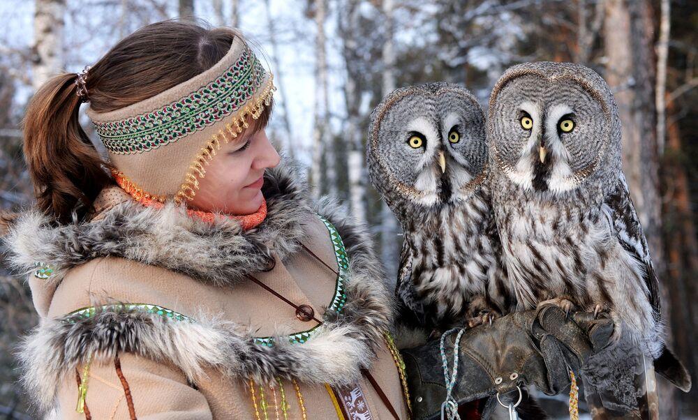 L'ornitologa Daria Koshcheyeva con i grandi gufi grigi durante l'allenamento allo zoo Royev Ruchey a Krasnoyarsk, Russia